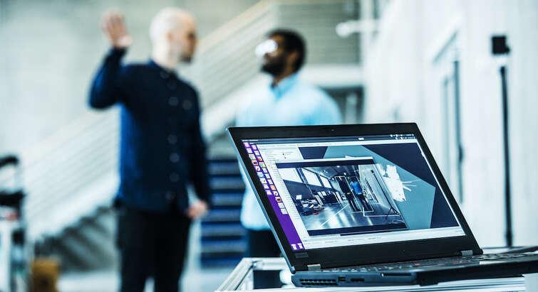 En computer med to mænd der snakker sammen i baggrunden